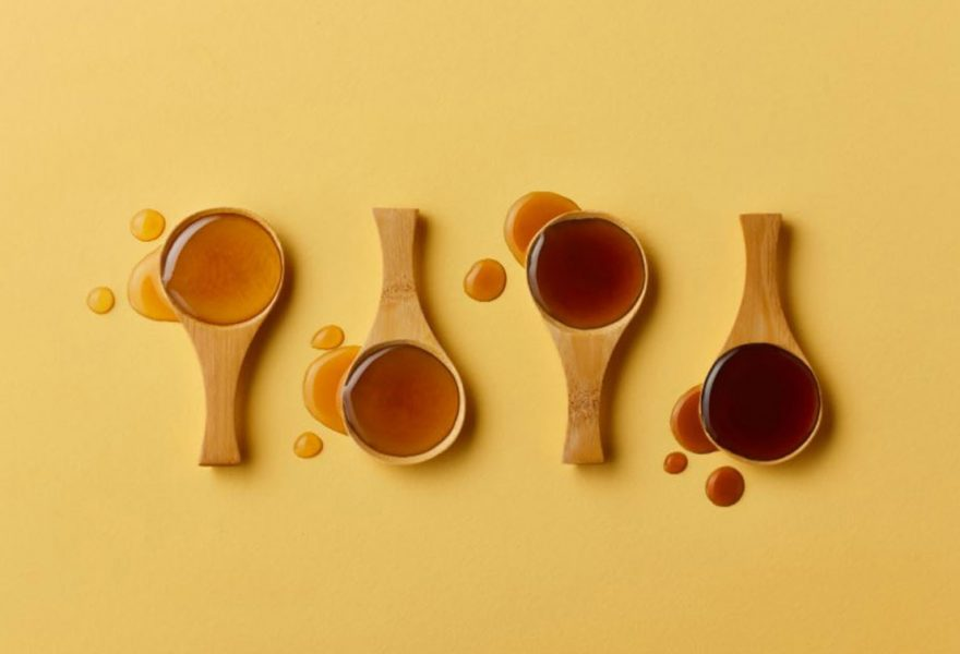 Spoons filled with maple syrup of new grades based on color and taste