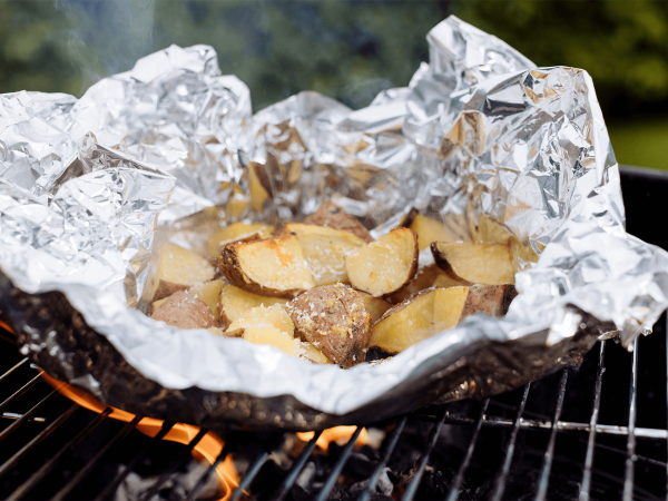 Maple parmesan garlic potato parcels on a grill in tinfoil