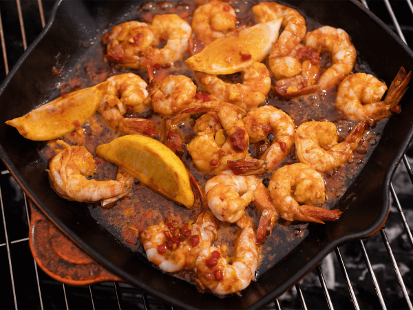 Sizzling maple king prawn in a skillet on a grill